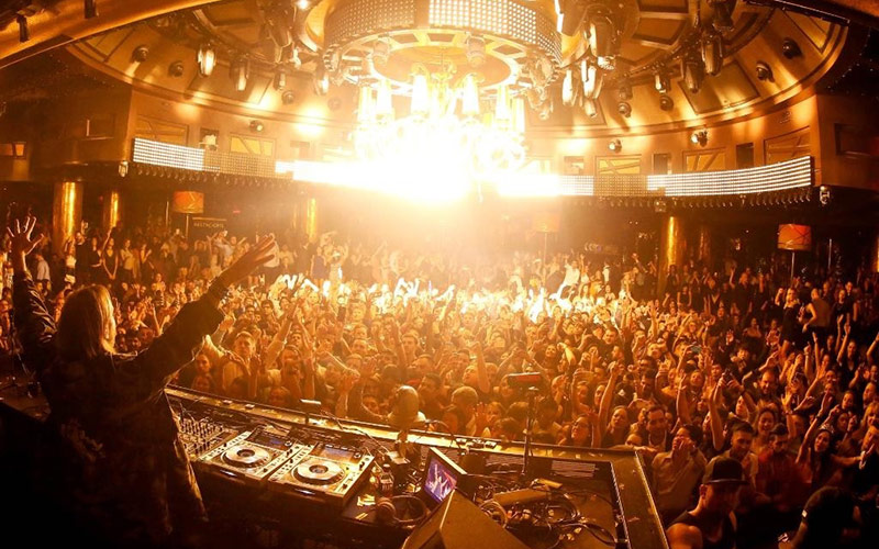 Vegas nightclub image behind the DJ booth in the main room plus crowd at XS.